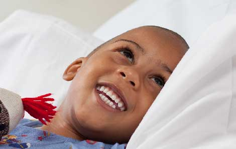 A boy smiling in a hospital bed.