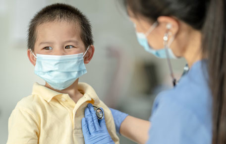 A doctor with face mask checking the heartbeat of a boy.