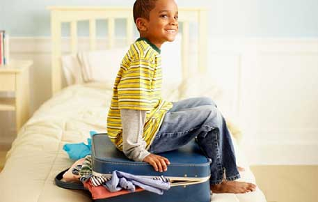 A child smiling and sitting on a suitcase on a bed. The suitcase has clothing spilling out of it.
