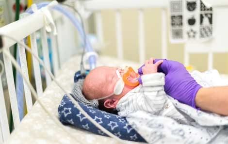 A baby in the intensive care unit holding the gloved hand of an adult healthcare provider.