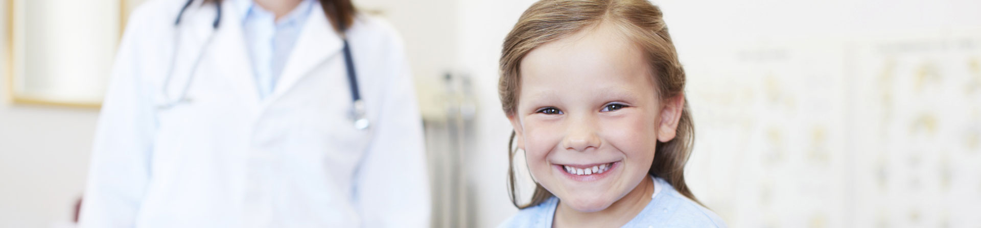 little girl smiling and her doctor