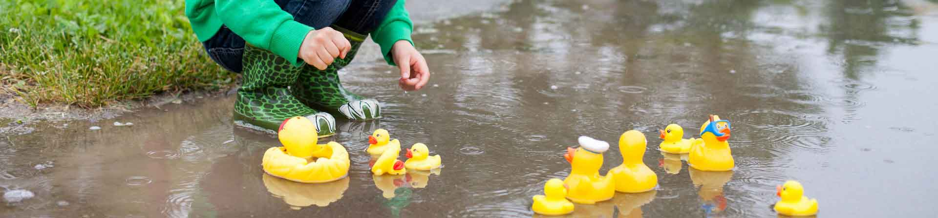 young child playing with rubber ducks in a puddle